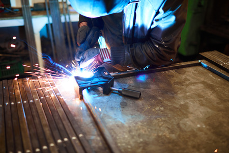 Arc welding in dark workshop Stock Photo