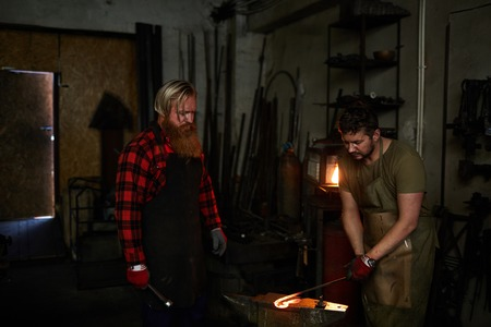 Skilled blacksmith teaching worker Imagens