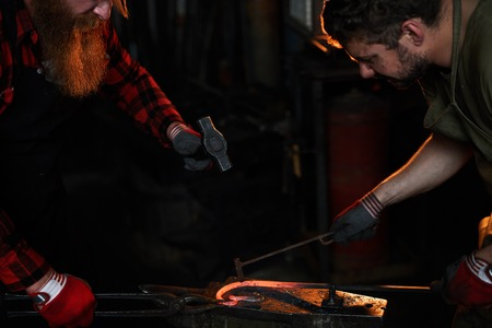 Team of blacksmiths shaping heated metal