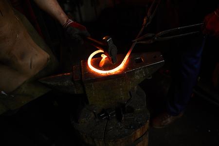 Hammering heated iron on anvil