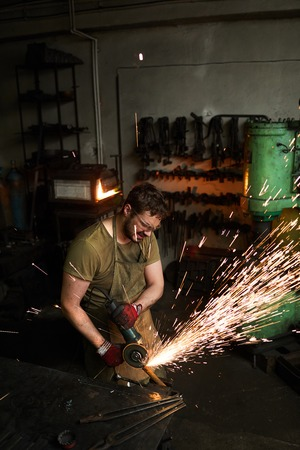 Busy strong blacksmith grinding metal Imagens