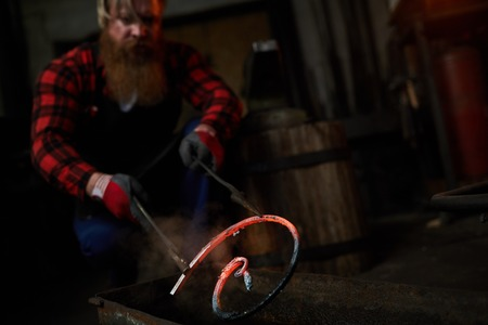 Brutal blacksmith holding metal bar in tongs