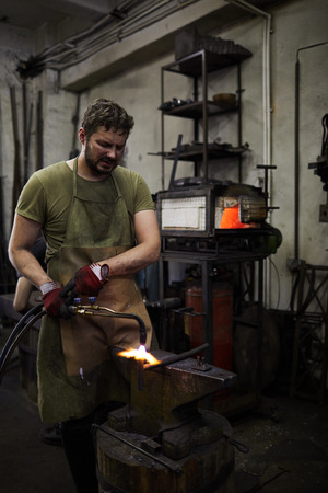 Frowning blacksmith parting metal with cutting torch Stockfoto