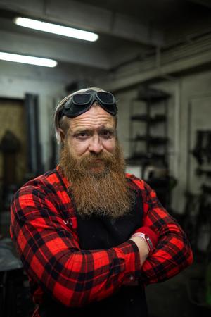 Scowling brutal blacksmith in workshop