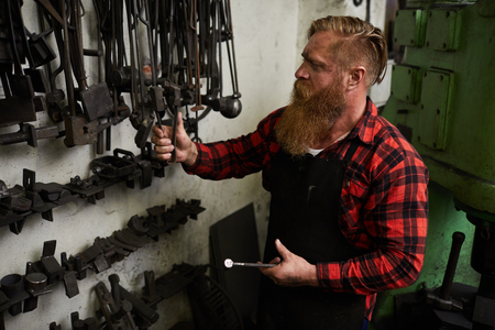 Busy blacksmith choosing tool for forging