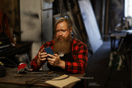 Frowning bearded blacksmith using smartphone