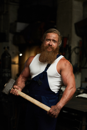 Brutal strong man with hammer Stockfoto