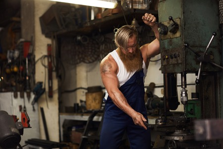 Powerful blacksmith with tattoo at work Stockfoto