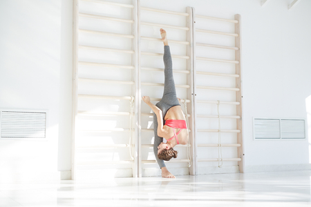 Fit woman stretching with gymnastic wall bars Banque d'images