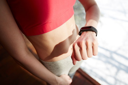 Anonymous sportswoman looking at fitness tracker