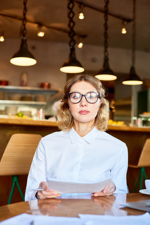 Serious woman in glasses sitting with papers