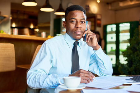 Black businessman speaking on phone in cafe