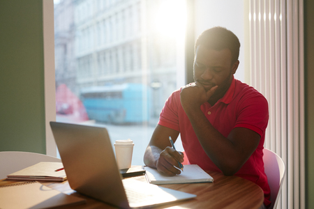 Black man with coffee working in morning