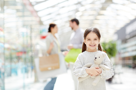 Charming girl in shopping mall with parents