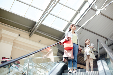 Woman with girl on moving stairs in mall