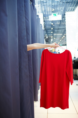 Crop hand holding dress in fitting room