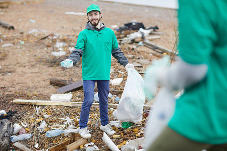 Smiling activist with rubbish bag Stock Photo
