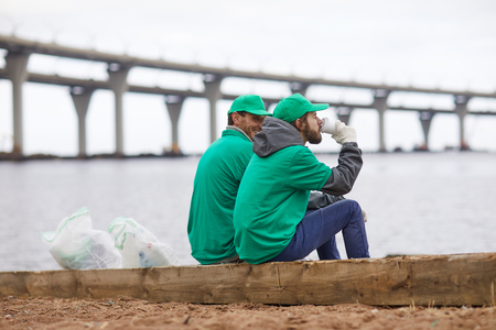 Volunteers with coffee on shore 写真素材