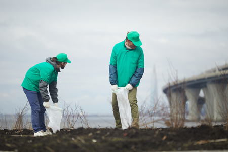 Men cleaning dirty shore Stock Photo