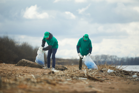 Men with bags collecting garbage