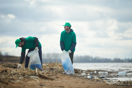 People working on polluted shore