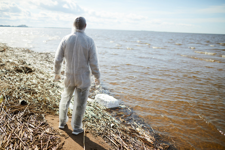 Man in protective suit on shore
