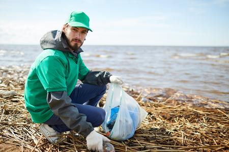Volunteer putting garbage to bag and looking at camera
