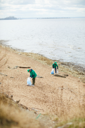 People collecting rubbish on shore