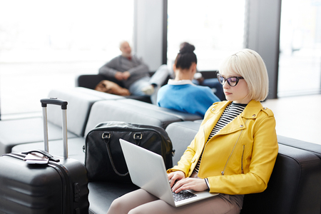 Young businesswoman with laptop in airport