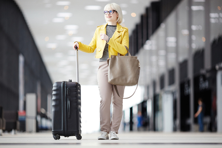 Woman standing with suitcase 스톡 콘텐츠 - 106502766