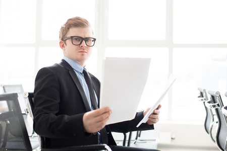 Puzzled businessman with paper documents