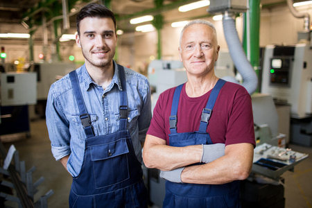 Two mechanics standing at factory