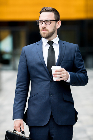 Man with plastic cup near office building Stock Photo