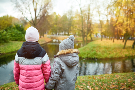 Back view of two school friends in warm jackets and beanies holding by hands while standing in front of waterside on autumn day