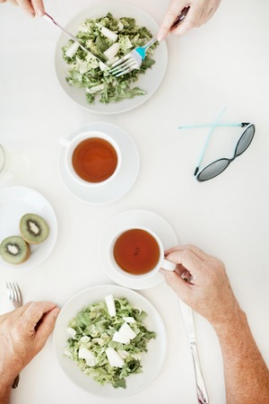 Overview of two cups of tea, sunglasses and two kiwi halves on table while humans eating fresh vegetarian salad