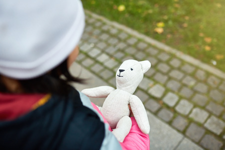White teddy held by girl in warm casualwear over trottoire in urban environment 写真素材