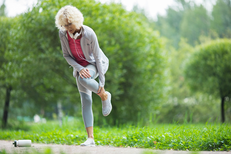 old woman hurting her leg while jogging