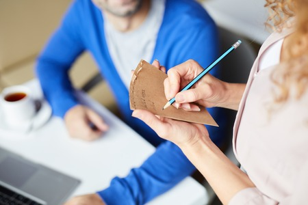 Close-up of unrecognizable waitress making notes about customers order in cafe, businessman working in cafe Stock Photo
