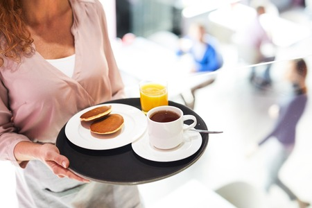 Close-up of unrecognizable waitress carrying tray with breakfast consisting of pancakes, coffee and orange juice, work in cafe