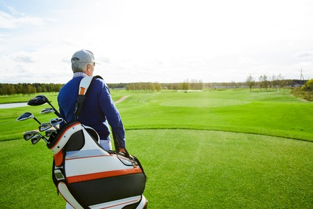 Man with golf clubs Stock Photo