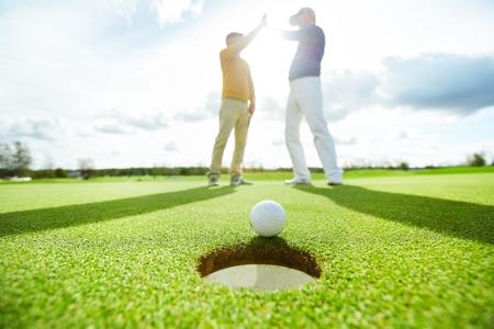 Golf ball by hole 스톡 콘텐츠