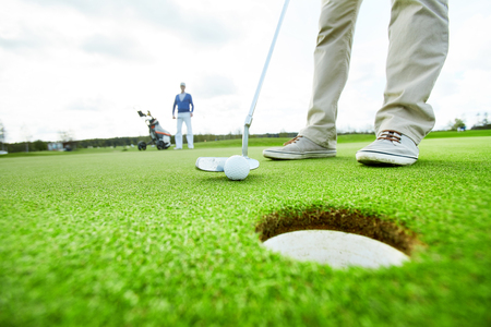 Golf player by hole Stock Photo