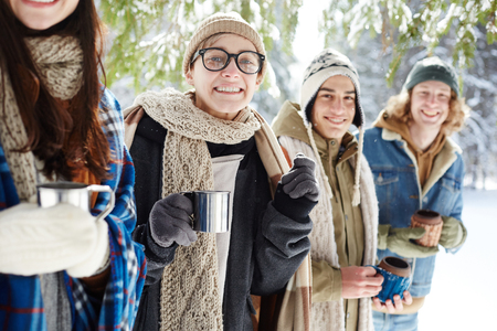 Group of young people smiling cheerfully at camera while posing in winter forest standing in row, focus on young woman holding metal cup Standard-Bild