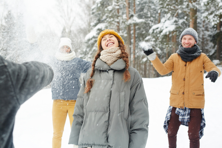 Cheerful young friends throwing snowballs at carefree girl in winter park: smiling pretty student girl enjoying leisure game in winter