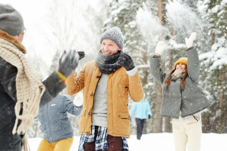 Jolly excited students having fun in winter park: cheerful guy in scarf gesturing hands while protecting from snowballs Stok Fotoğraf
