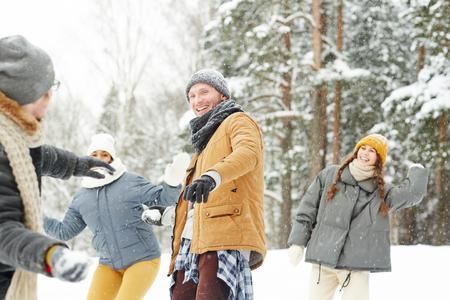 Amis insouciants profitant d'une bataille de boules de neige : jeune homme joyeux et excité jetant une boule de neige et regardant un ami dans un parc d'hiver