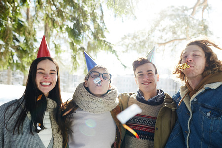 Group of happy young people celebrating Christmas outdoors in beautiful forest, all wearing party caps