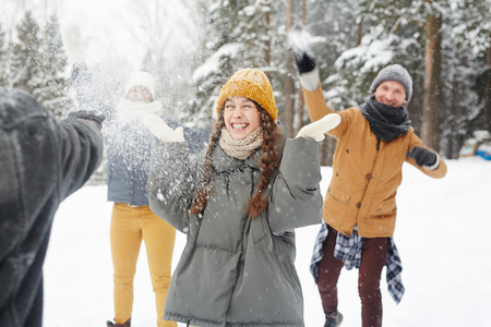 Happy young friends in winter coats having snowball fight in forest: excited girl standing in center and feeling snow on face Stock Photo