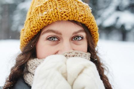 Retrato de contenido hermosa niña con ojos verdes con gorro de punto y bufanda escondiendo la nariz para calentarla mientras camina en invierno