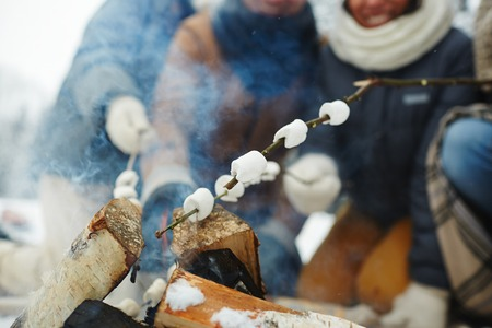 Close-up of unrecognizable people enjoying camping: they making roasted marshmallows on fire in winter Stock fotó